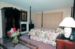 The Traditional Room features a 4 poster queen sized bed, a fireplace, and a whirlpool tub for 2.